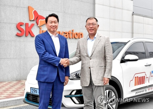Hyundai Motor Group Executive Vice Chairman Chung Euisun (right) shakes hands with SK Group Chairman Chey Tae-won at SK Innovation's electric vehicle battery plant in Seosan, South Chungcheong Province, in July. (Hyundai Motor)