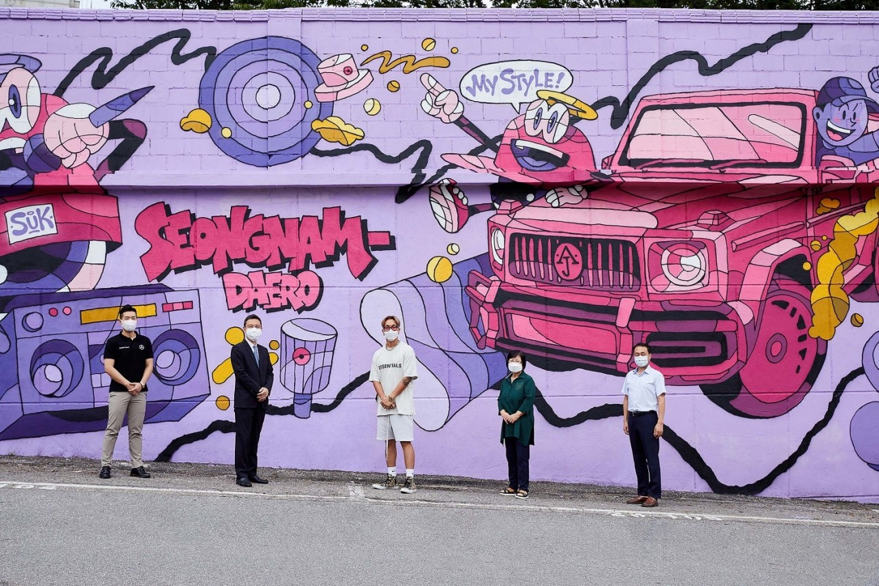 Artist Artime Joe (center), branch manager of Han Sung Motor's Seongnam exhibition hall Choi Soo-han (second from left) and participants pose for a photo in front of the mural near the exhibition hall Sept. 1. (Han Sung Motor)