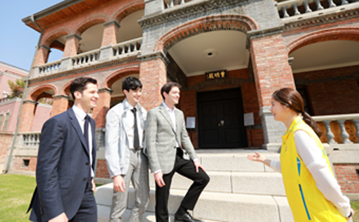 Foreign-born TV celebrities -- (from left) Alberto Mondi, Robin Deiana and Daniel Lindemann -- listen to a local tour conductor for their activities as honorary ambassadors for Jeong-dong, Seoul, at a historic building near the palace Deoksugung in April 2018. (Seoul's Jung-gu Office)