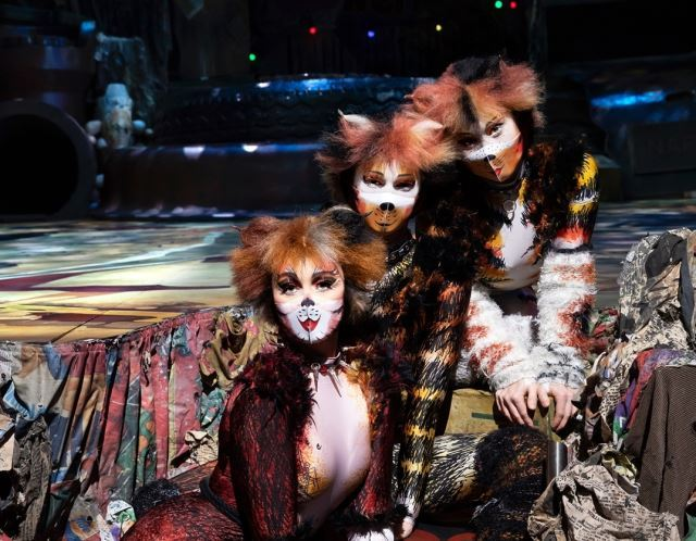 "Three ""Cats"" cast members wear masks featuring catlike makeup. (S&Co)"