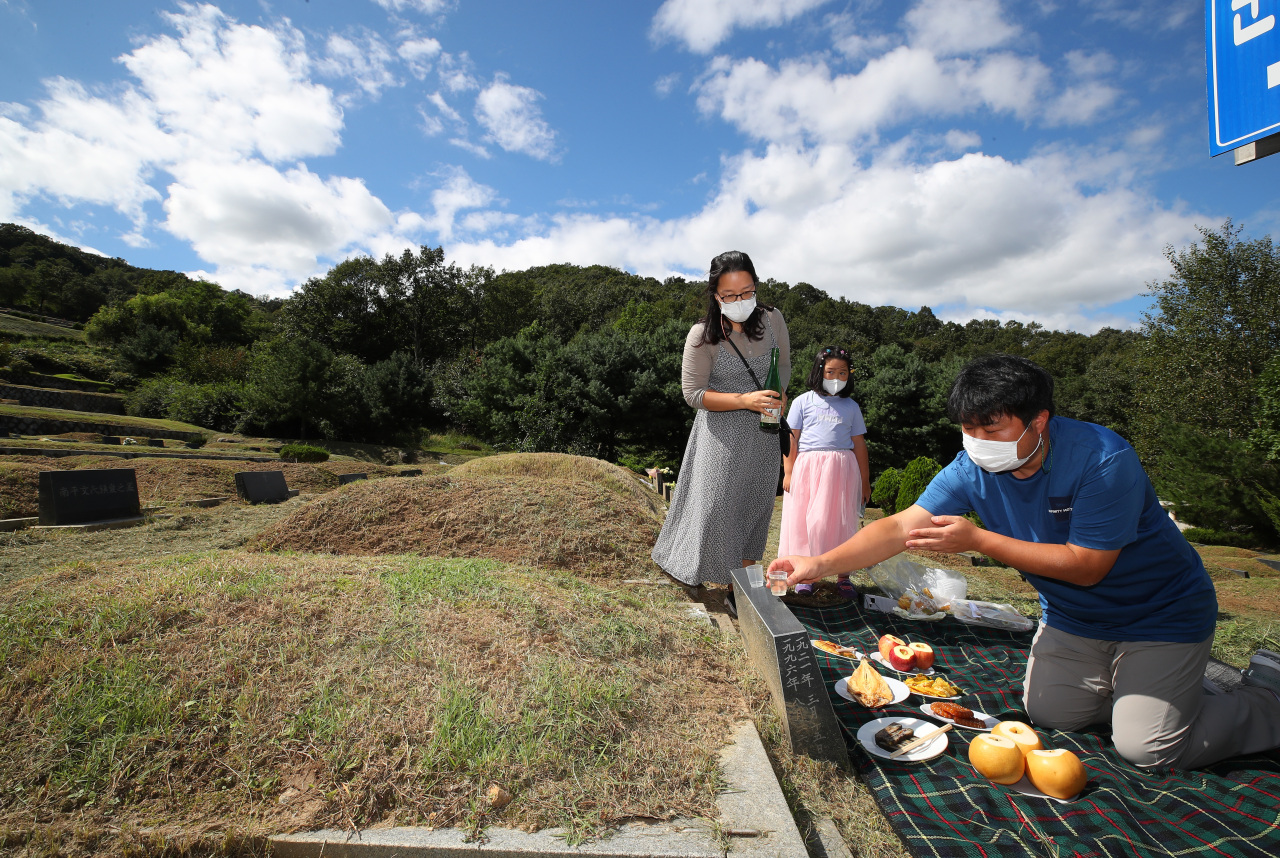 A family pays a visit to ancestral graves at a memorial park in Paju, Gyeonggi Province, Sunday. (Yonhap)