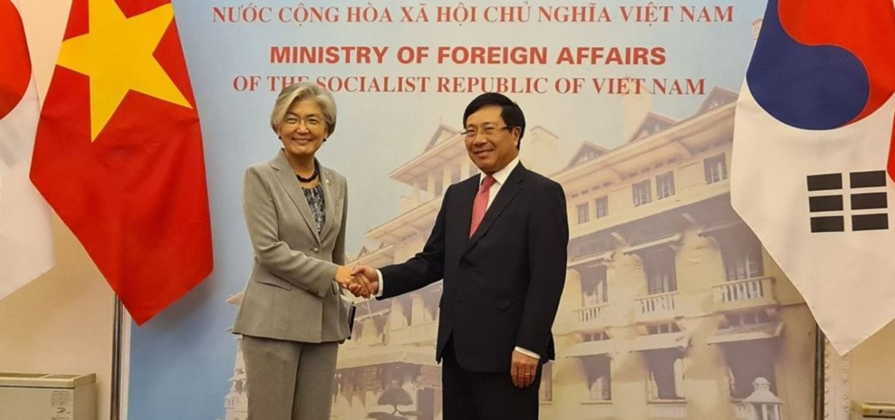 Foreign Minister Kang Kyung-wha (left) shakes hands with her Vietnamese counterpart, Pham Binh Minh, before their talks in Hanoi on Sept. 18, 2020. (Yonhap)