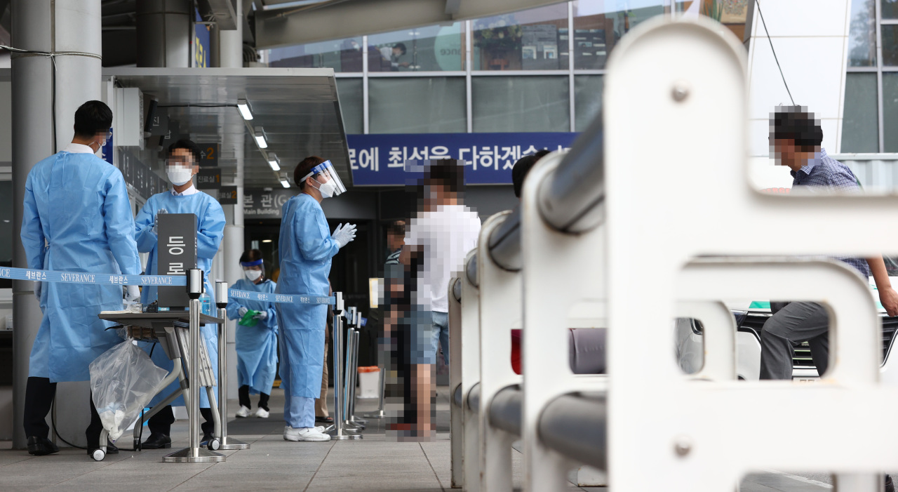 Medical staff and health officials talk to visitors at a treatment booth stationed at Yonsei Severance Hospital in Seoul on Thursday. (Yonhap)