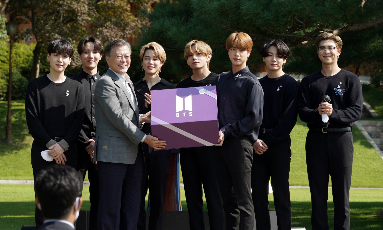 President Moon Jae-in receives a gift from BTS during the inaugural ceremony of the Youth Day on Saturday. (Yonhap)