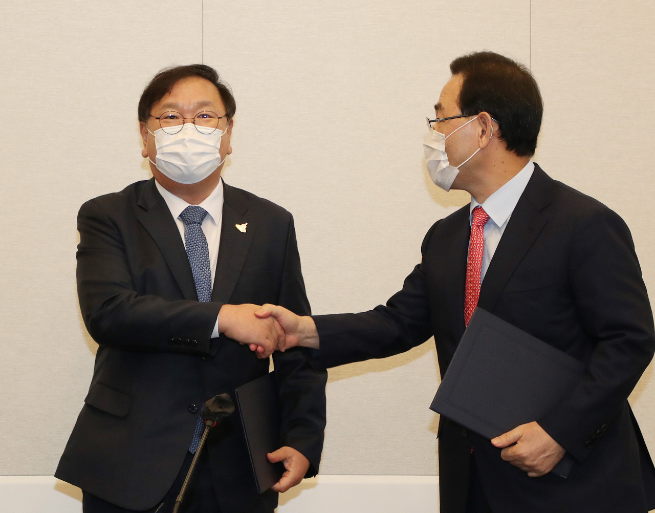 Democratic Party floor leader Rep. Kim Tae-nyeon and People Power Party floor leader Rep. Joo Ho-young shake hands after reaching an agreement on Tuesday. (Yonhap)