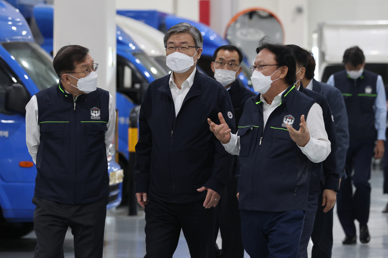 CJ Logistics CEO Park Keun-hee, right, briefs Labor Minister Lee Jae-kap, center, during the minister's visit to the parcel delivery firm's sorting center in Gimpo, Gyeonggi Province, on Wednesday. (Yonhap)