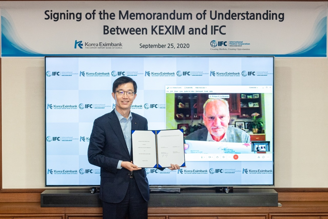 The Export-Import Bank of Korea Chairman Bang Moon-kyu (left) poses at a signing ceremony with IFC Chief Executive Philippe Le Houerou during a virtual meeting held Friday to sign a memorandum of understanding. (Eximbank)