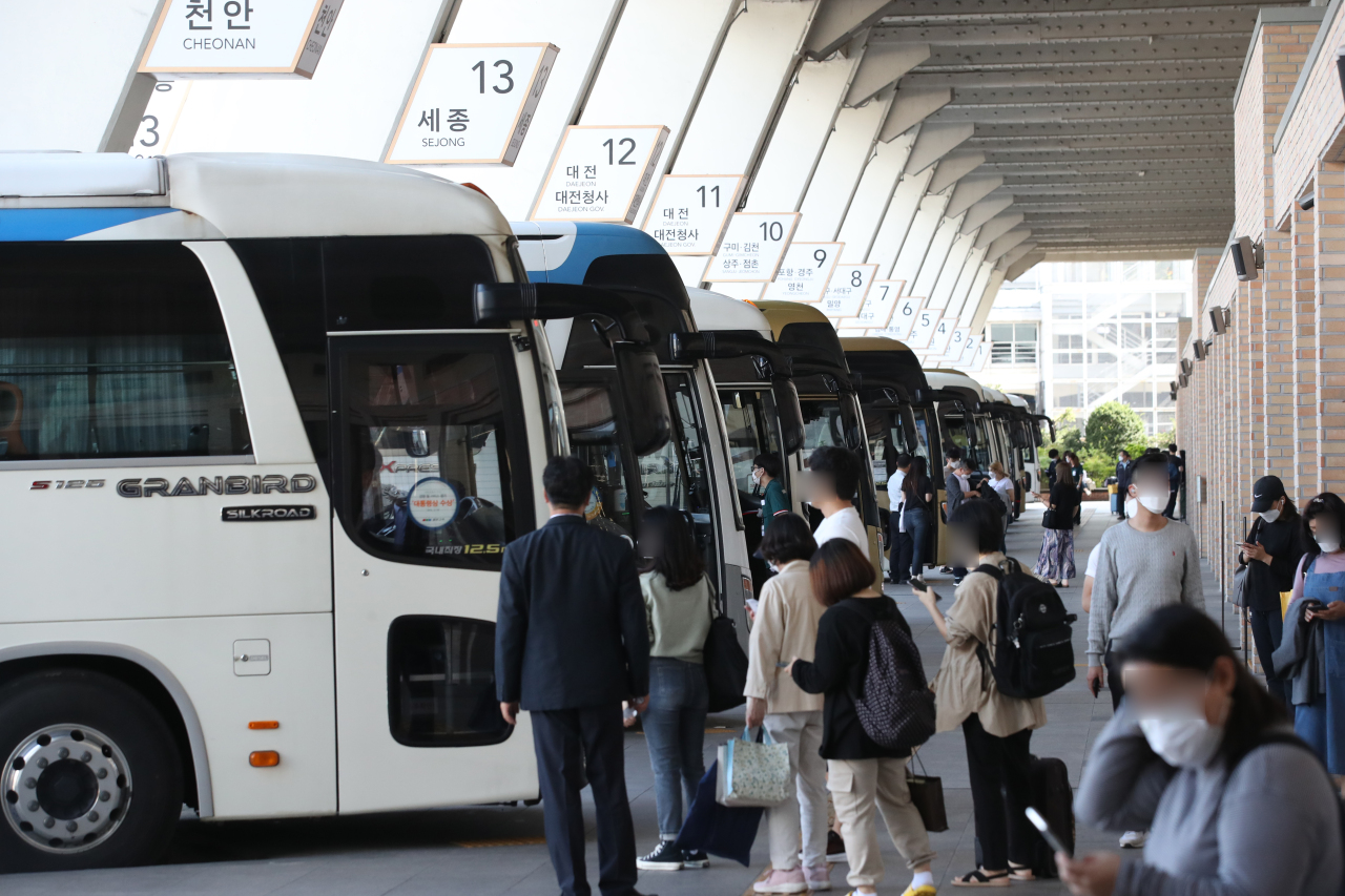 Passengers board buses Sunday at the Seoul Express Bus Terminal ahead of the Chuseok holiday period starting Wednesday. (Yonhap)