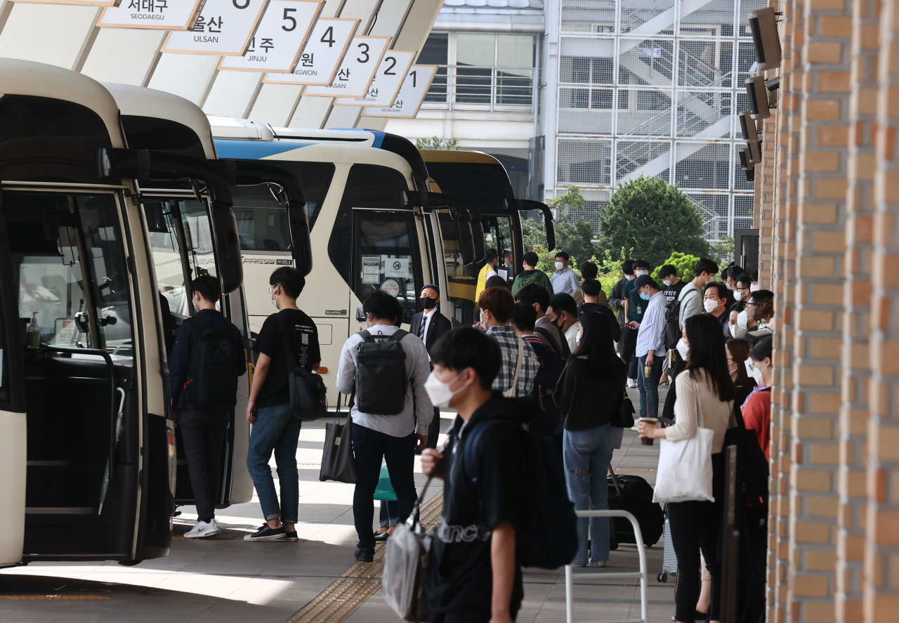 Travellers board buses at a terminal in Seoul on Tuesday. (Yonhap)