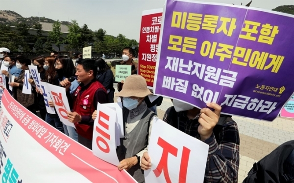 Activists demand that the government pay emergency relief funds to foreigners living here as well, at a press conference in Seoul in May. (Yonhap)