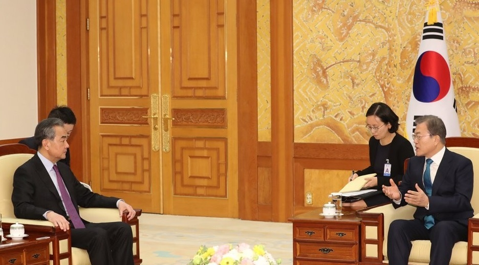 This file photo taken Dec. 5, 2019, shows South Korean President Moon Jae-in (R) talking with China's State Councilor Wang Yi at Cheong Wa Dae in Seoul. (Yonhap)