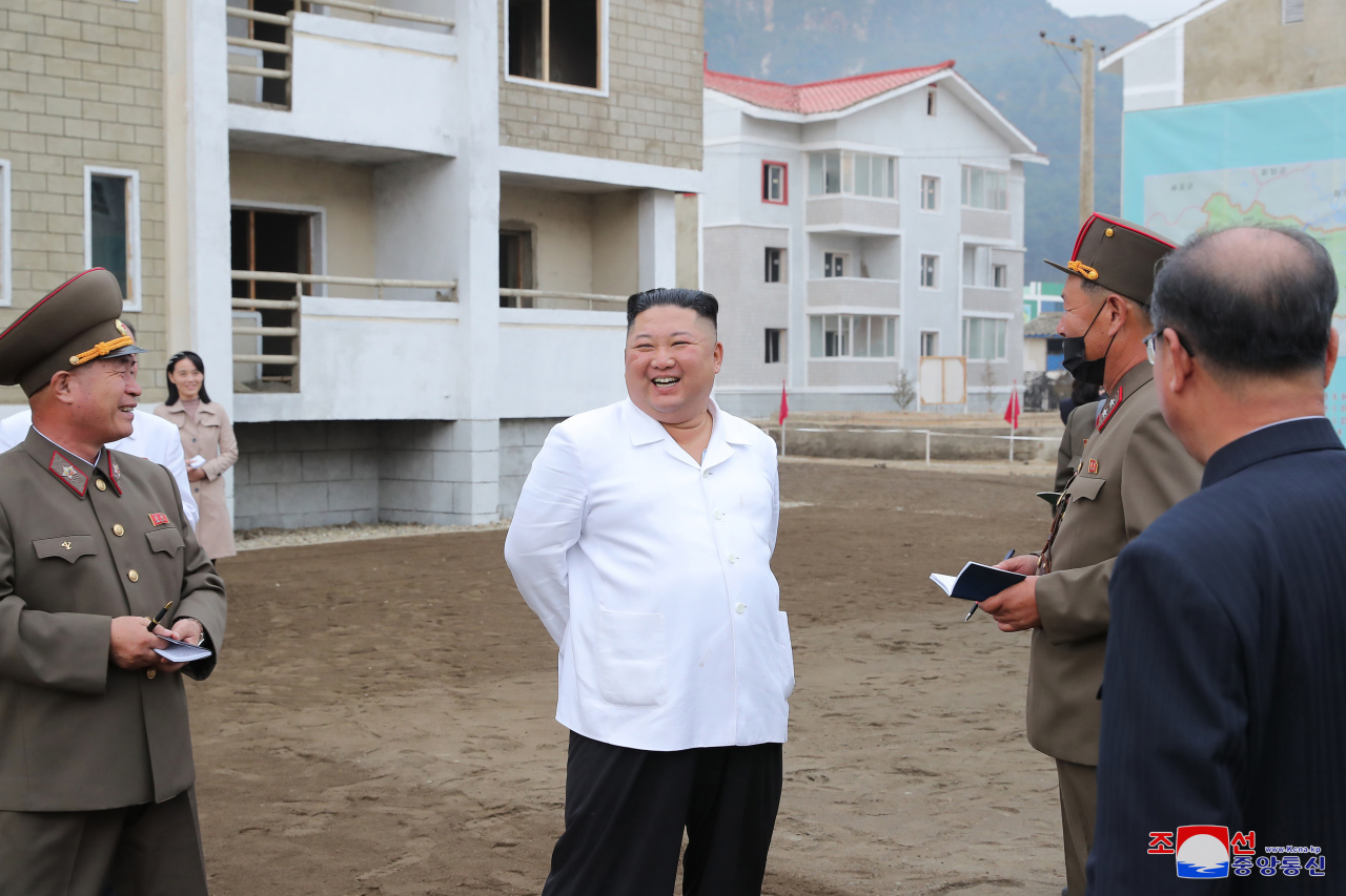North Korean leader Kim Jong-un (center) smiles as he talks to officials during a visit to the reconstruction site in the central border county of Kimhwa, Gangwon Province, in this photo provided by Rodong Sinmun on Oct. 2, 2020. He was accompanied by Kim Yo-jong (second from left), his younger sister and first vice department director of the ruling Workers' Party's Central Committee. (Rodong Sinmun)