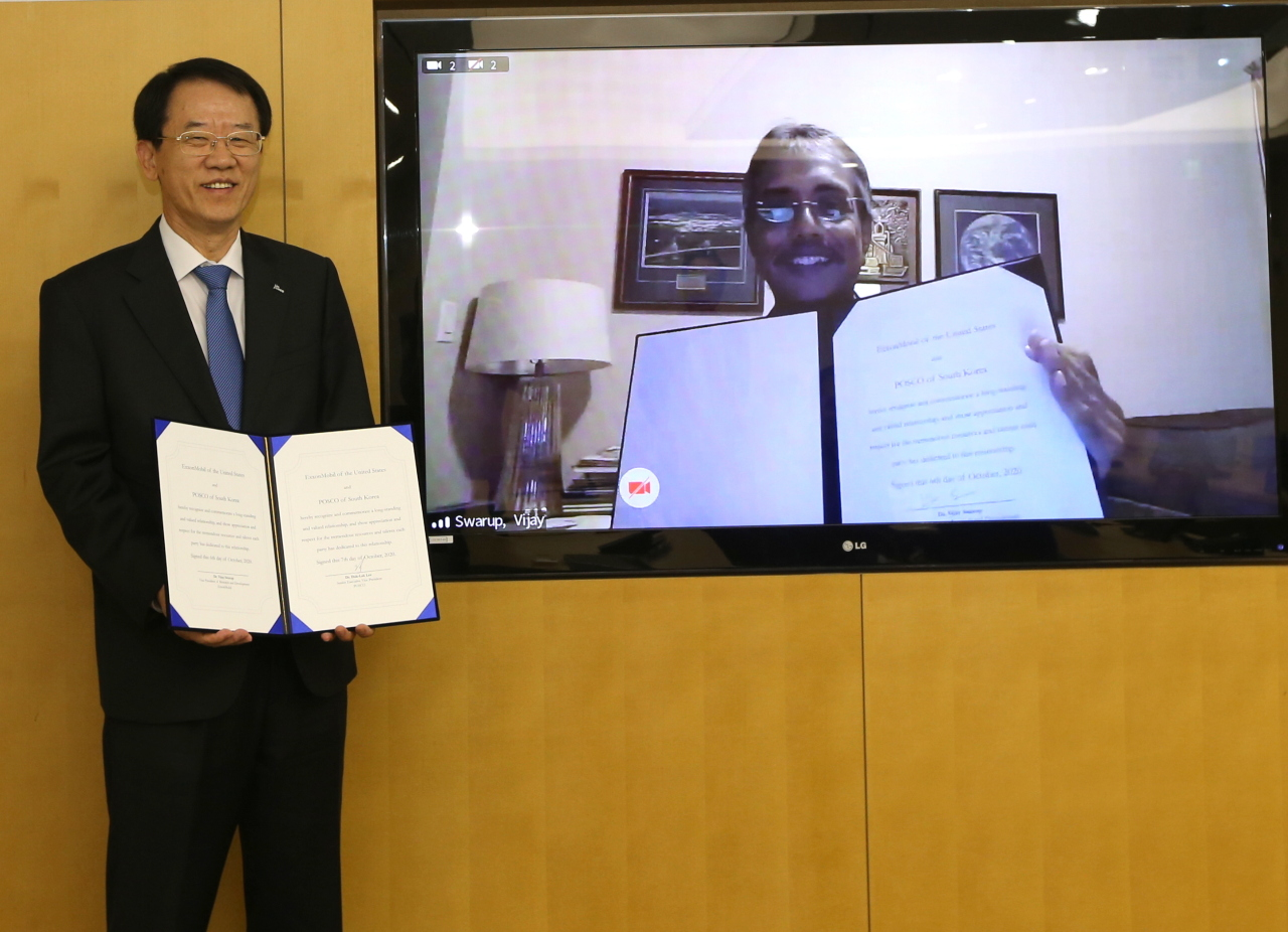 Posco Research Institute President Lee Duk-lak (left) and ExxonMobil Research and Engineering Vice President Vijay Swarup pose Wednesday during the inking ceremony. (Posco)
