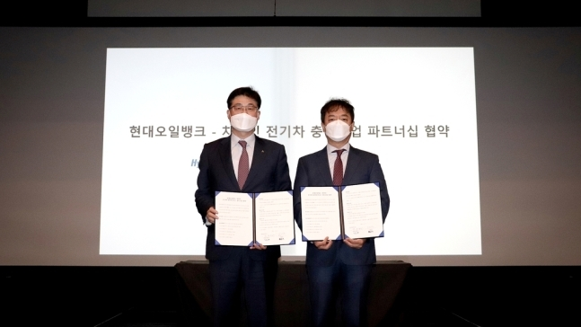 Han Hwan-gyu (left), a sales director at Hyundai Oilbank, and Choi Young-seok, chief strategy officer at Charzin, pose during a partnership signing event Wednesday. (Hyundai Oilbank)