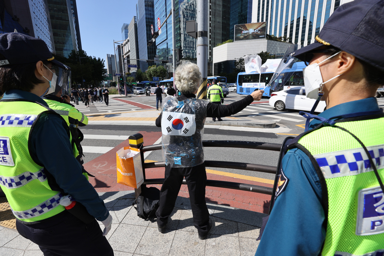 A woman holds a single-person protest in Jongno-gu, central Seoul, on Friday after officials banned mass rallies from virus fears. (Yonhap)