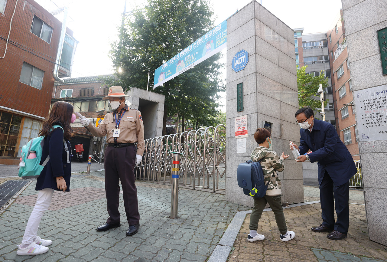 Seoul elementary school children have their temperatures checked and hands sanitized on Monday morning. (Yonhap)