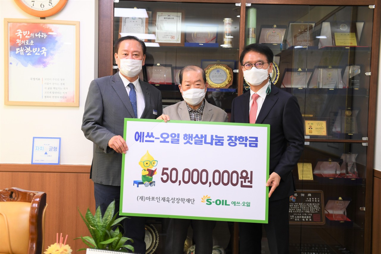 From right: S-Oil President Ryu Yul, Mapo Scholarship Foundation President Park Hong-seop and Mapo-gu Office head Yoo Dong-gyun pose for a photo at a donation ceremony at the Mapo-gu Office in western Seoul on Thursday. (S-Oil)