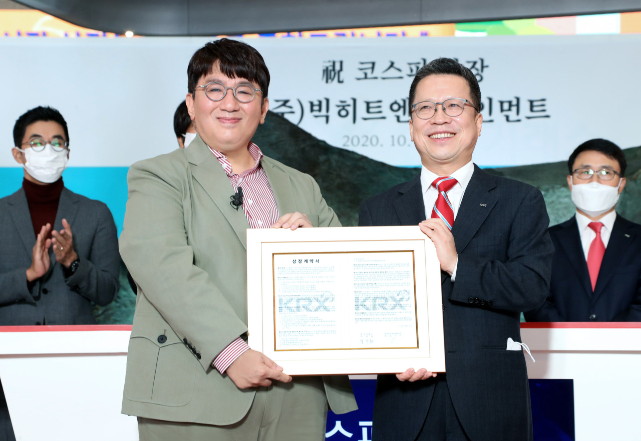 Korea Exchange CEO Jung Ji-won (right) and Big Hit Entertainment CEO Bang Si-hyuk pose at the management agency's listing ceremony held at the KRX headquarters in Seoul on Thursday. (Korea Exchange)