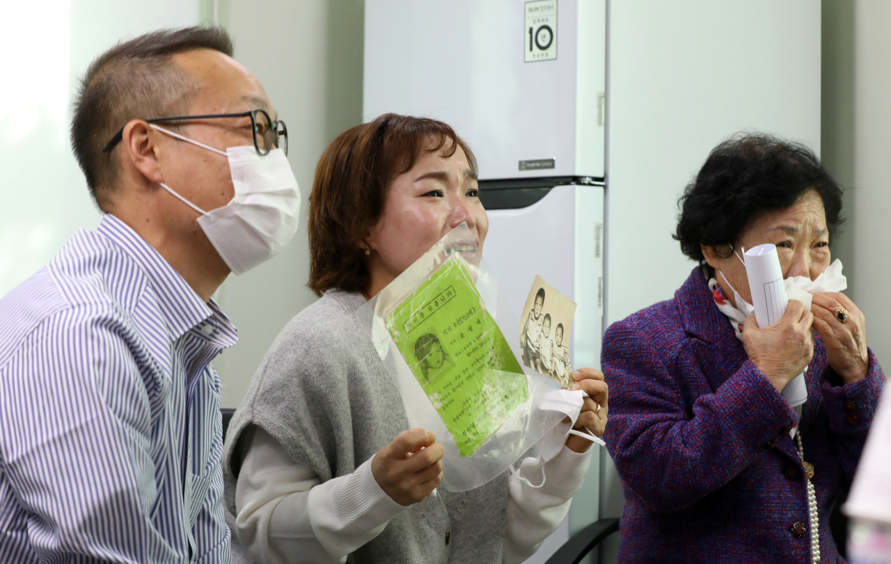 Yoon Sang-hee (center), twin sister of Yoon Sang-ae, a Korean-born adoptee who is now an American citizen, holds a photo and a poster during a reunion held via a video call in Seoul on Thursday. (Yonhap)