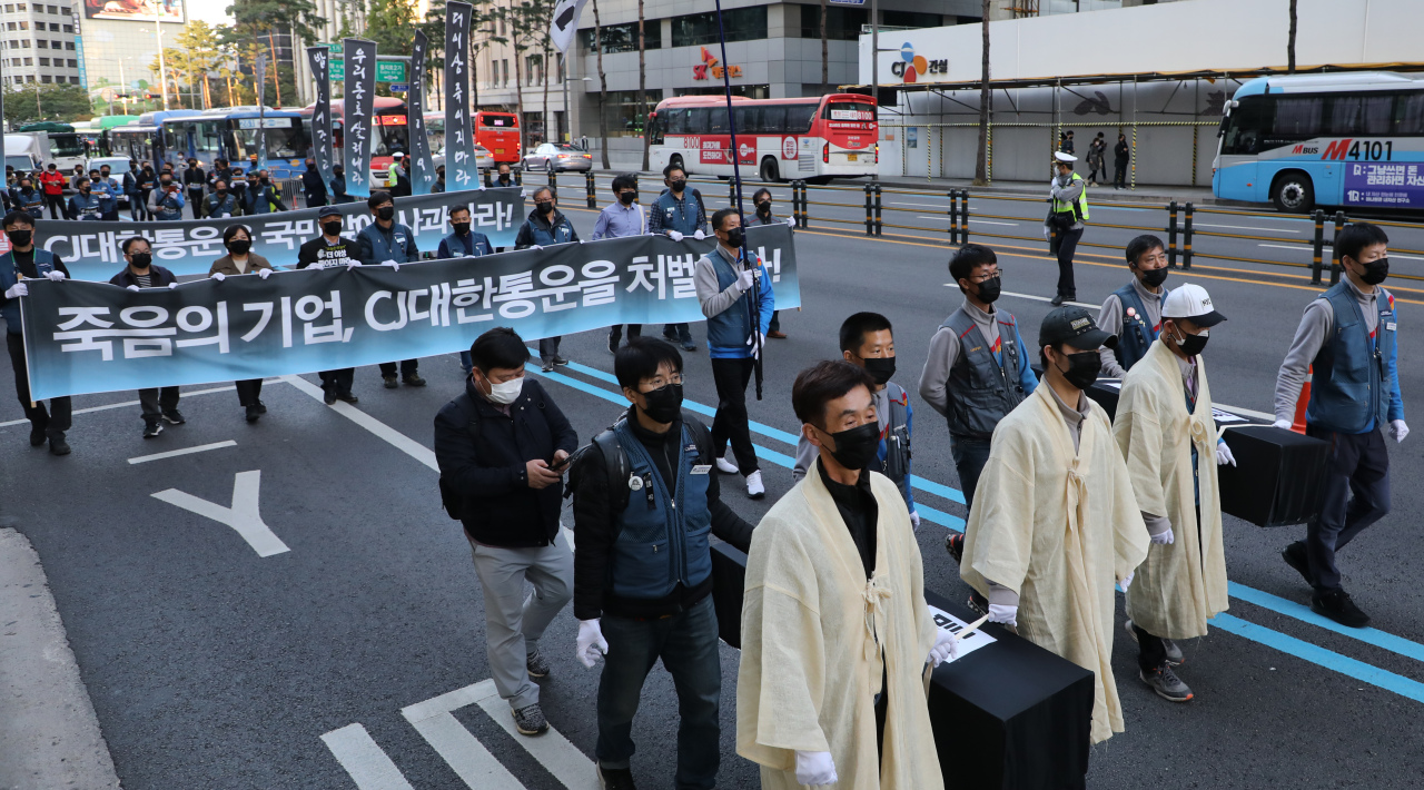 An alliance for the rights of parcel delivery workers stage a memorial march Saturday in central Seoul for delivery workers who died from overwork and fatigue. (Yonhap)