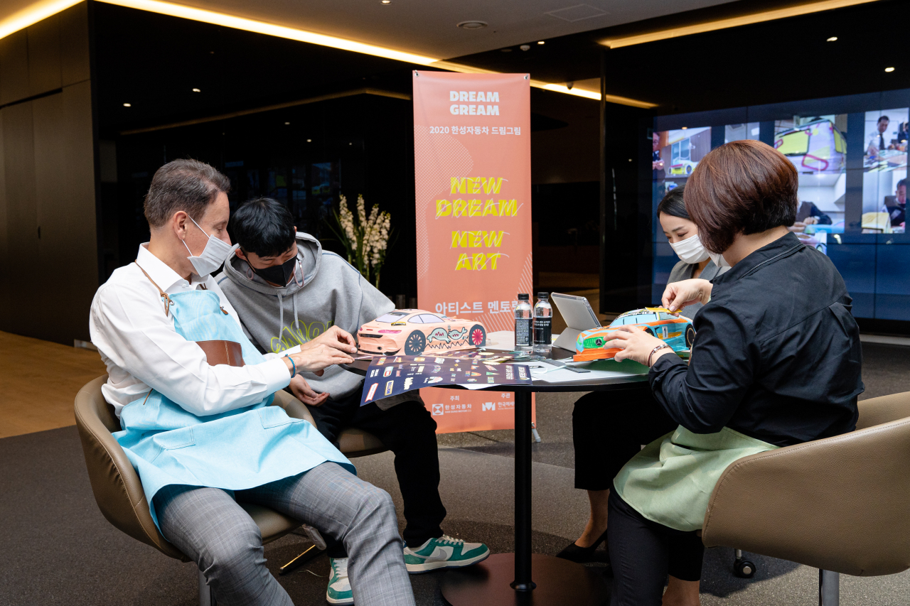 """Han Sung Motor CEO Ulf Ausprung (left) works on """"dream art cars"""" with tape artist Park Gun-woo during the Dream Gream Ambassador event held in the company's Cheongdam showroom in Seoul on Friday. (Han Sung Motor)"""