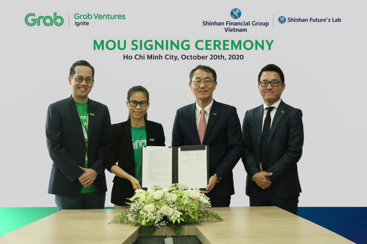 Shin Dong-min, head of Shinhan Bank Vietnam (second from right) and Nguyen Thai Hai Van, managing director of Grab Vietnam (second from left), pose for a photo Tuesday after signing a memorandum of understanding to cooperate on the digital transformation of financial services, at the Grab Vietnam headquarters in Ho Chi Minh City. (Shinhan Financial)