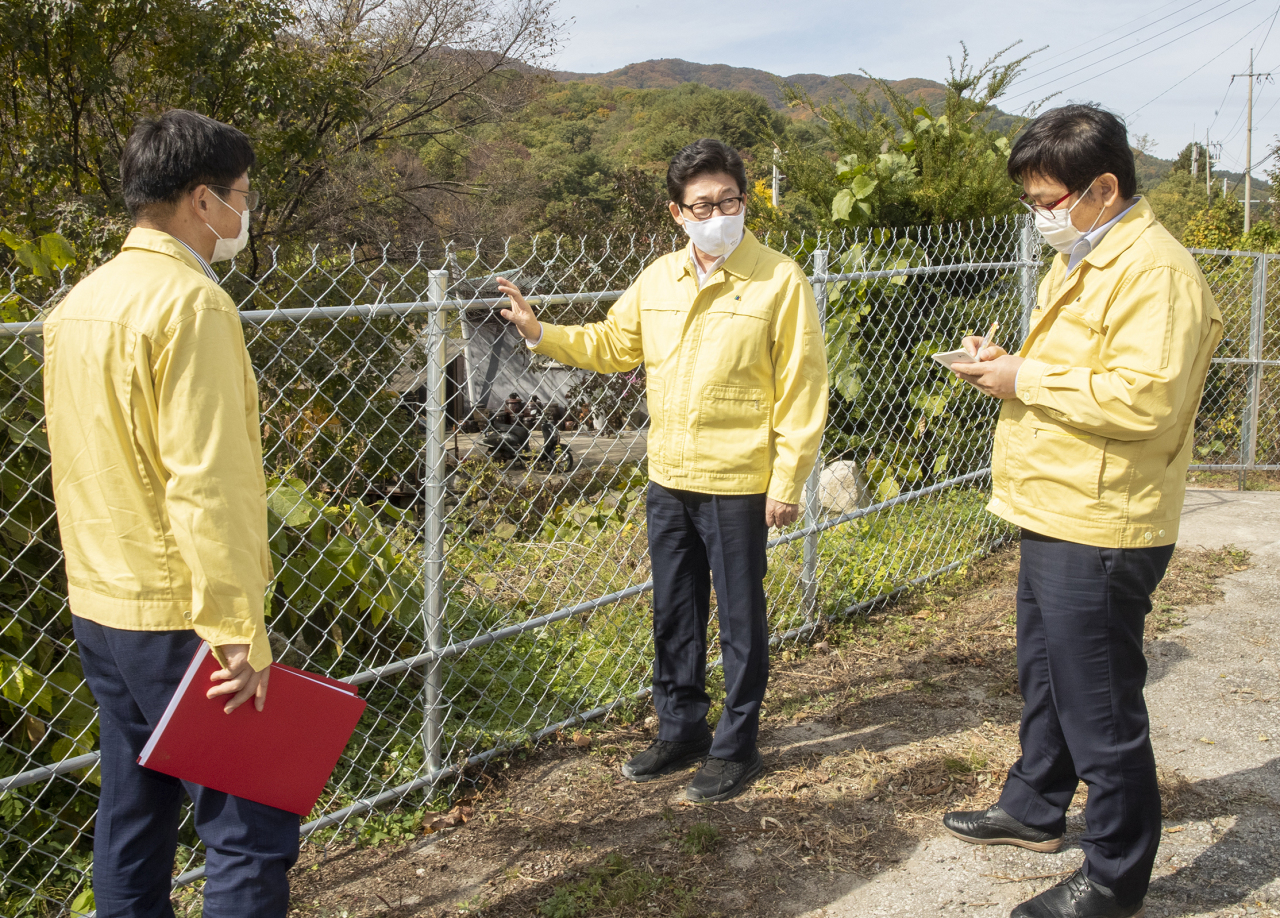 Environment Minister Cho Myung-rae checks a fence in Hwacheon, Gangwon Province, installed to prevent movement of wild boars in the area as a means to contain the spread of the African swine fever. (Ministry of Environment)