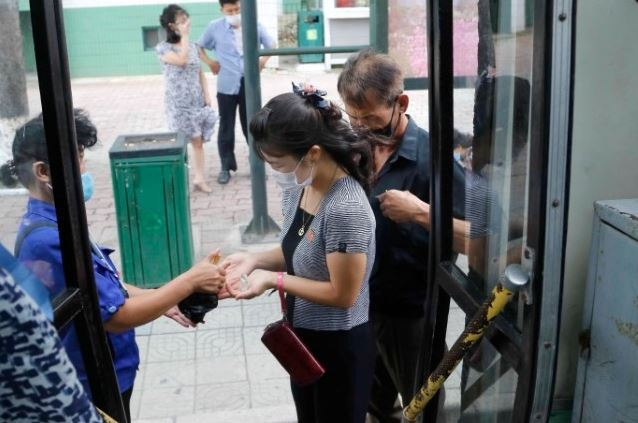 A passenger wearing a face mask to help curb the spread of the coronavirus has her hands disinfected before getting on a trolley bus in Pyongyang on Aug. 13. (AP)