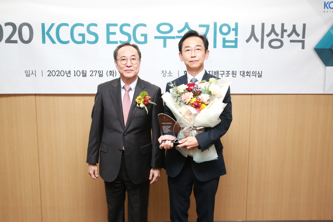 Posco International's management support division chief Lee Yong-seok (right) and Korea Corporate Governance Service President Shin Jhin-young pose for a photo at a ceremony held Tuesday in Seoul. (Posco International)