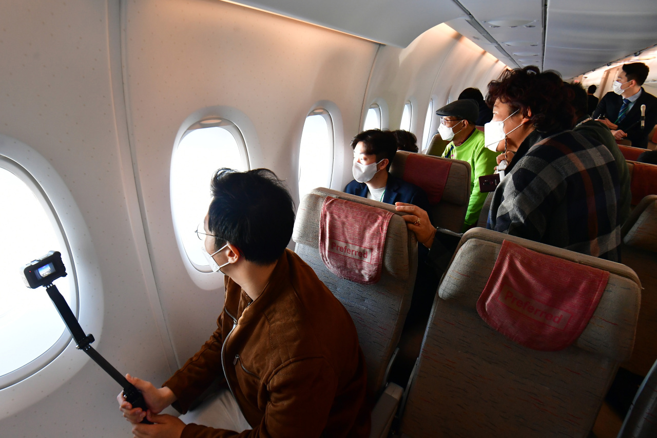 Passengers on Asiana's A380 flight to nowhere on Saturday lean toward the windows to enjoy the view. (Yonhap)