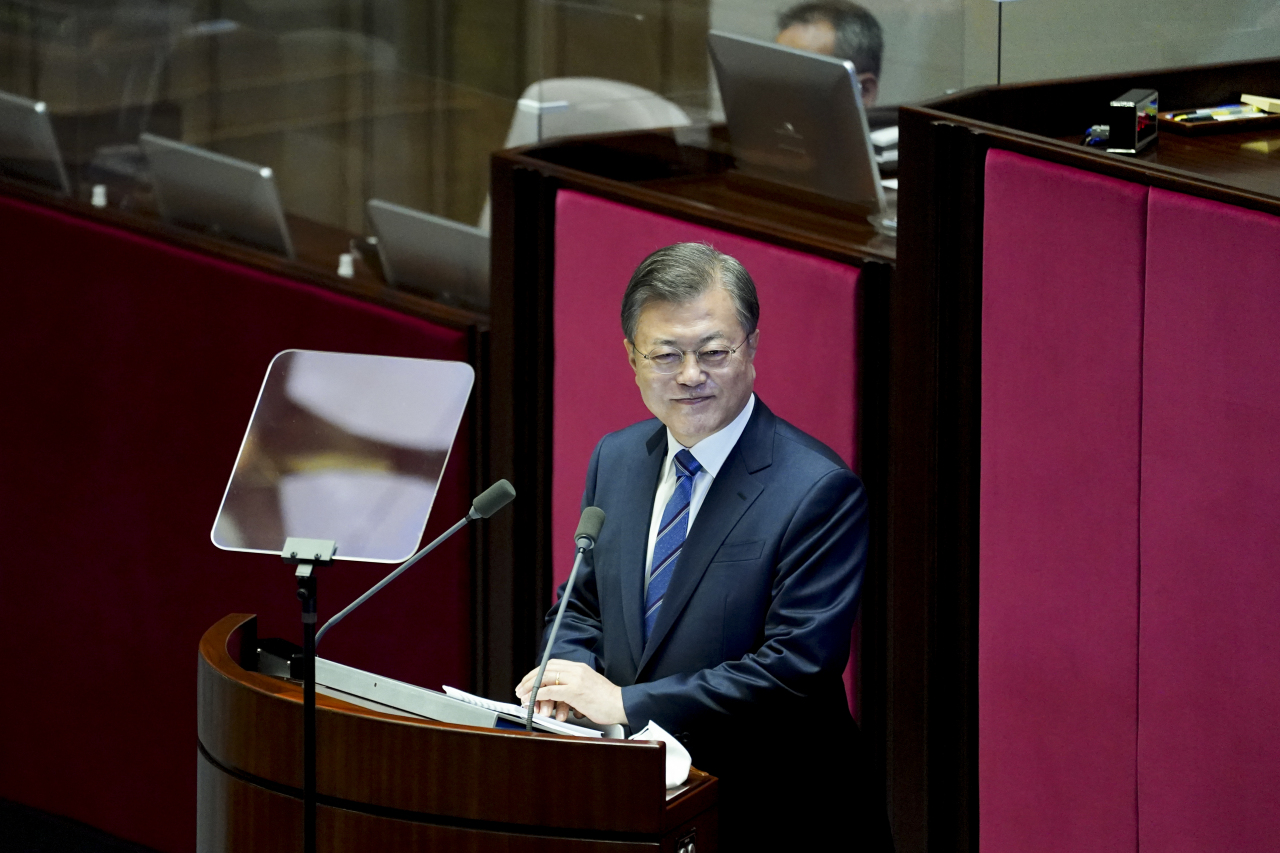 President Moon Jae-in looks at protesting opposition lawmakers during his parliamentary address on Wednesday. (Yonhap)