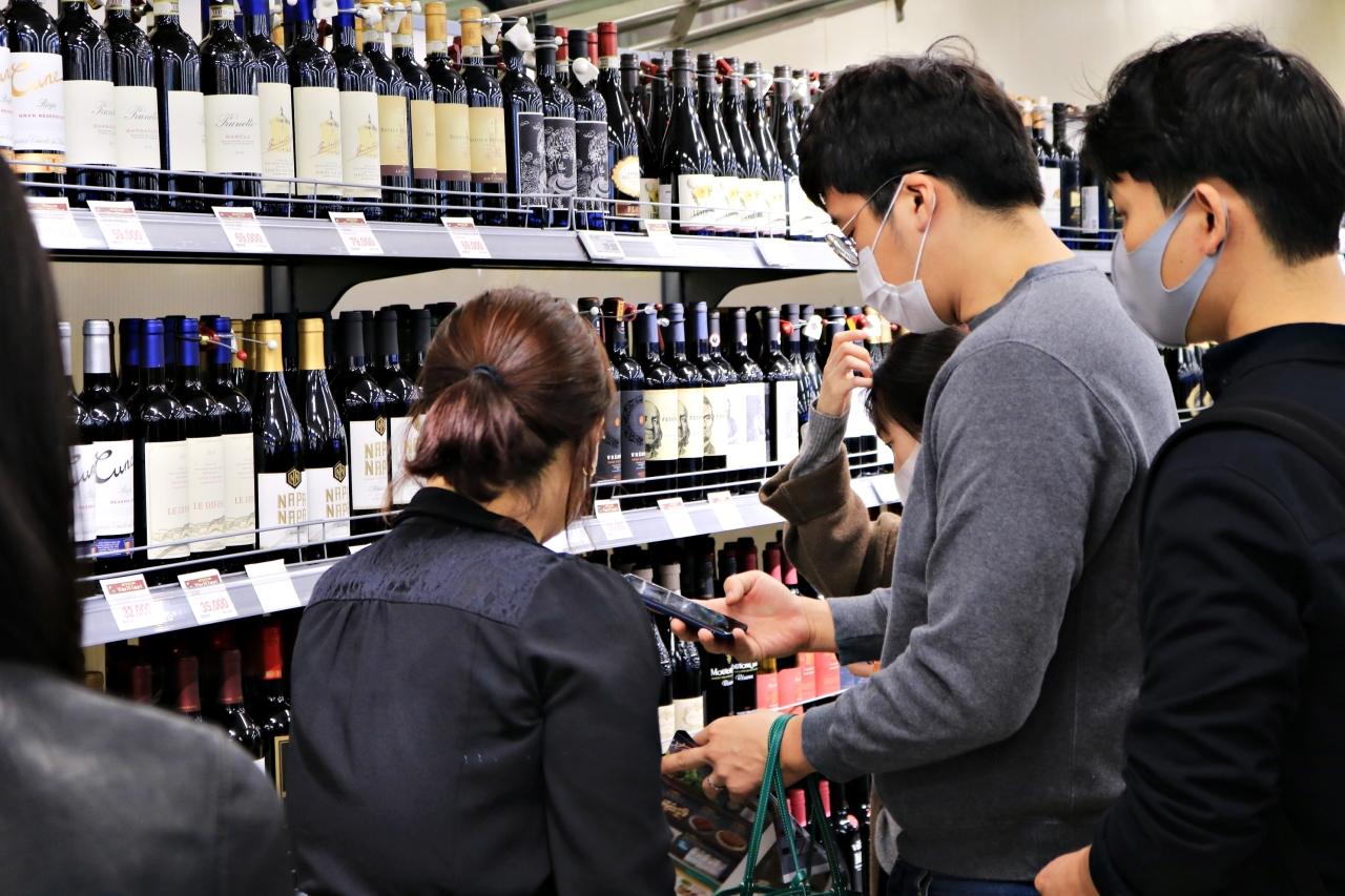 Customers flock to wine bottles displayed at a wine shopping event in October at the E-mart discount store in Yongsan, Seoul. (Son Ji-hyoung/The Korea Herald)