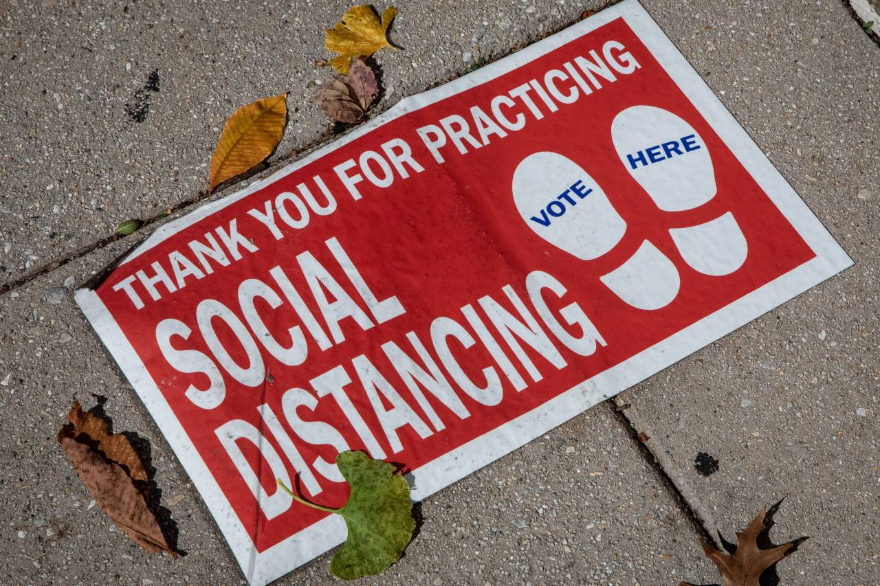 A social distancing sign is seen on the ground outside a voting location on Monday in Washington DC. Preparations continue throughout Washington DC ahead of the Nov. 3 US presidential election with many business owners boarding up and securing their shops in precaution to protests and rioting. (AFP-Yonhap)