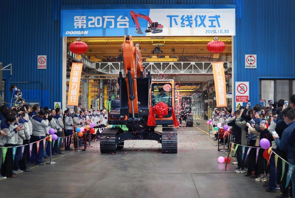 A ceremony is held to mark the production of the 200,000th excavator last Friday, at Doosan Infracore China Co. (DICC), Doosan Infracore Co.'s Chinese unit, located in Yantai, Shandong Province. (Doosan Infracore)
