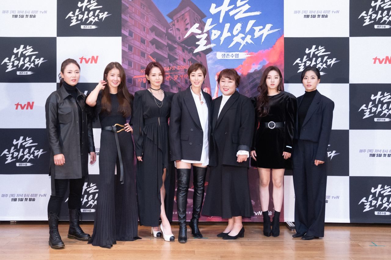 "Instructor Park Eun-ha (left) and the six celebrities who appear on ""I'm a Survivor"" pose for photos during an online press conference Wednesday. (CJ ENM)"