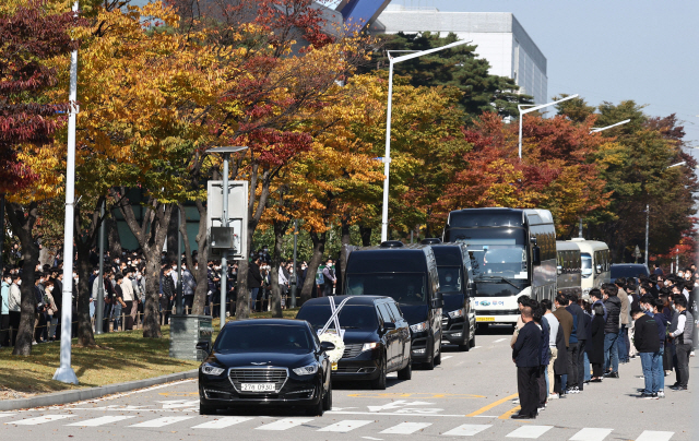 A hearse carrying the coffin of late Samsung Group chief Lee Kun-hee and other vehicles exit Samsung Electronics' chip plant in Hwaseong, south of Seoul, last Wednesday as Samsung employees line up to mourn the death of their longtime chairman. (Yonhap)