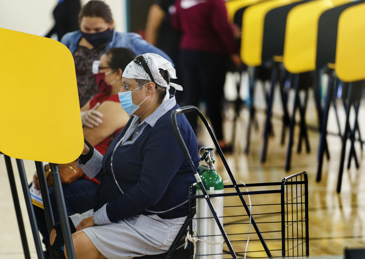 East Los Angeles resident Christi Campos who suffers from chronic obstructive pulmonary disease, COPD, uses a portable oxygen tank while sitting to cast her ballot in-person on Election Day at the Ruben F. Salazar Park recreation center, an official vote center in East Los Angeles, Tuesday. (AP-Yonhap)