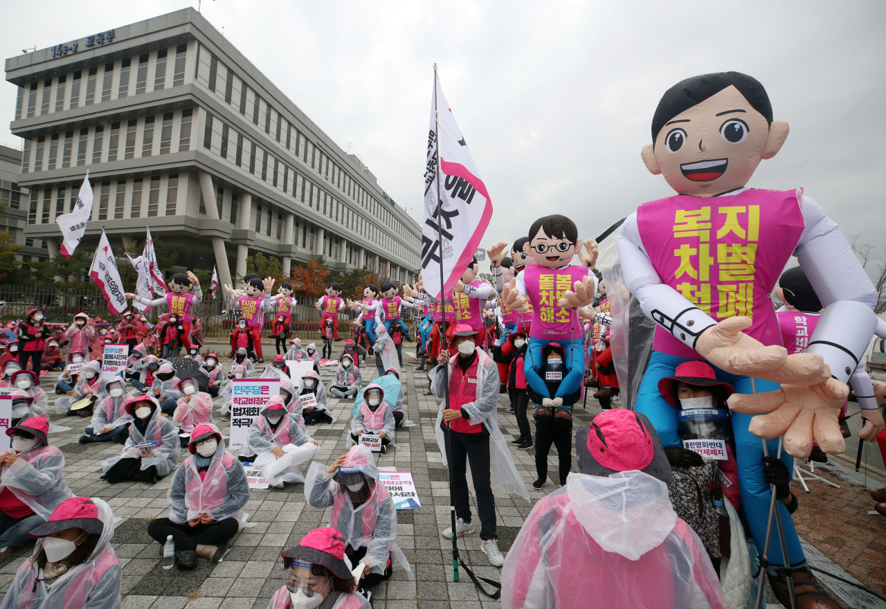 After-school care attendants stage a rally Friday in front of the Ministry of Education building in Sejong as they stage a one-day strike in protest of the ministry`s legislative revision plans. (Yonhap)