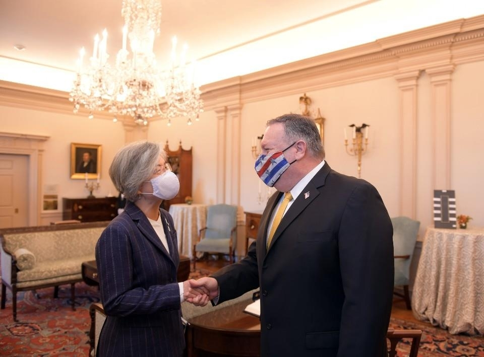 In the photo provided by South Korea's foreign ministry, South Korean Foreign Minister Kang Kyung-wha (L) and US Secretary of State Mike Pompeo shake hands during a meeting in Washington on Monday. (Ministry of Foreign Affairs)