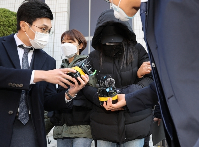 The mother, who is suspected of abusing a 16-month-old adoptee, heads to a prison van on Wednesday. (Yonhap)