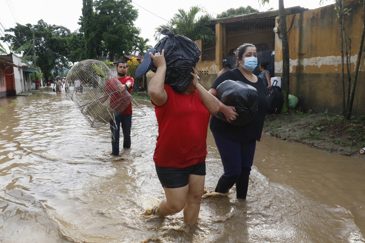 Residents carrying belongings wade through floodwaters in the neighborhood of Suyapa, Honduras, Thursday, Nov. 5. The storm that hit Nicaragua as a Category 4 hurricane on Tuesday had become more of a vast tropical rainstorm, but it was advancing so slowly and dumping so much rain that much of Central America remained on high alert. (AP-Yonhap)
