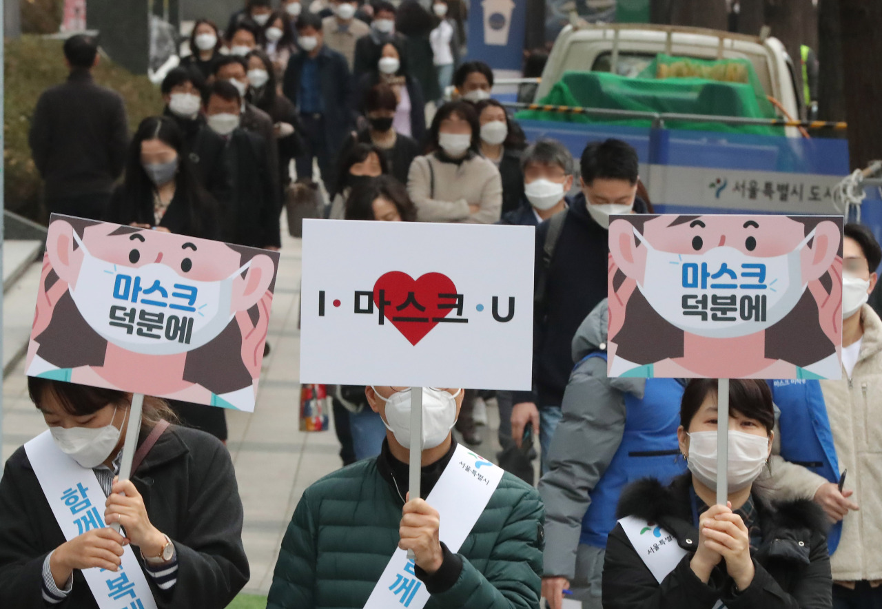 Seoul city officials carry signs urging citizens to wear a face mask in downtown Seoul on Friday. (Yonhap)
