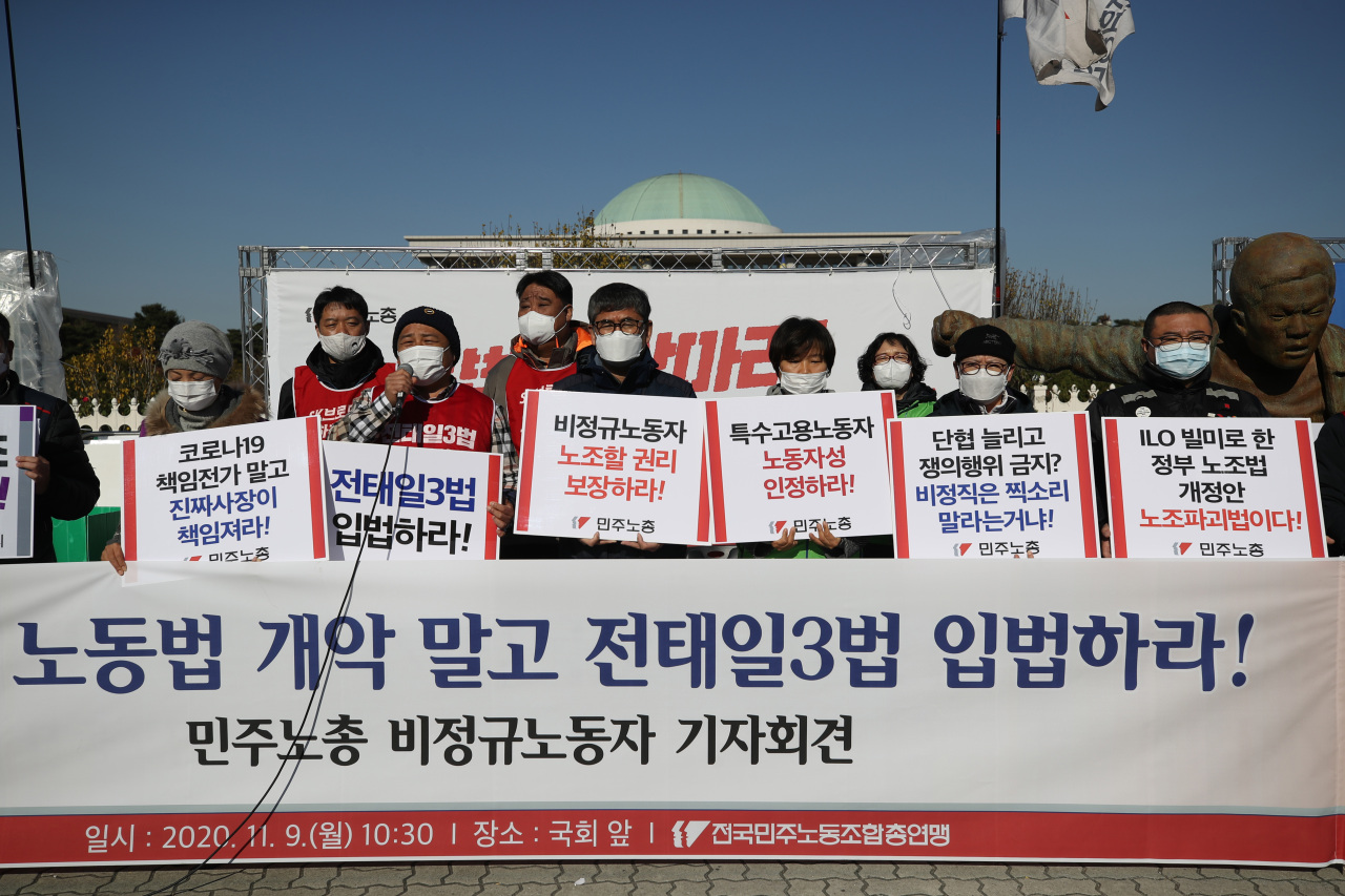 Members of the Korean Confederation of Trade Unions call on lawmakers to legislate labor rights protections during a press conference held in front of the National Assembly building in Yeouido, central Seoul, on Monday. (Yonhap)