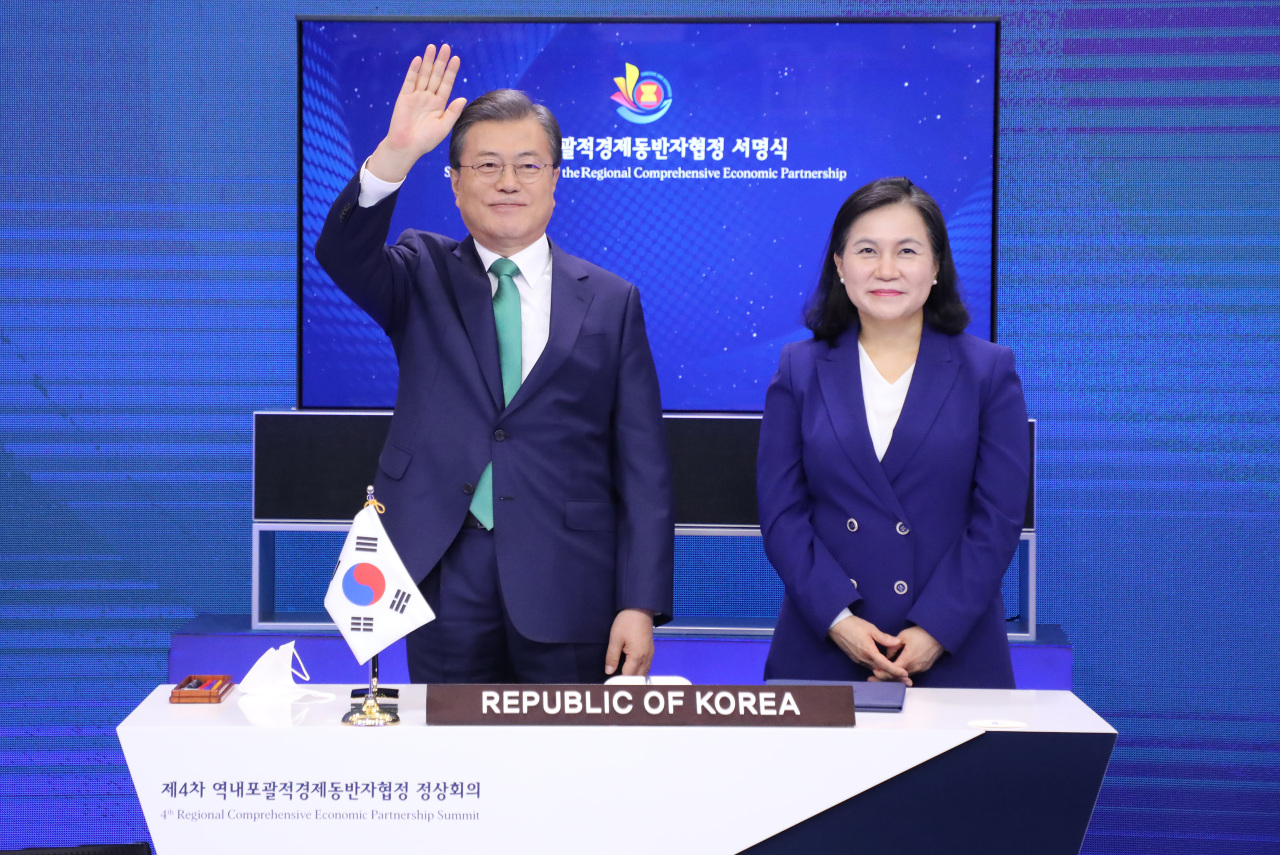 South Korean President Moon Jae-in (L) waves to leaders of other nations, with Trade Minister Yoo Myung-hee standing next to him, during the signing ceremony of the Regional Comprehensive Economic Partnership (RCEP) agreement at Cheong Wa Dae in Seoul on Sunday. (Yonhap)