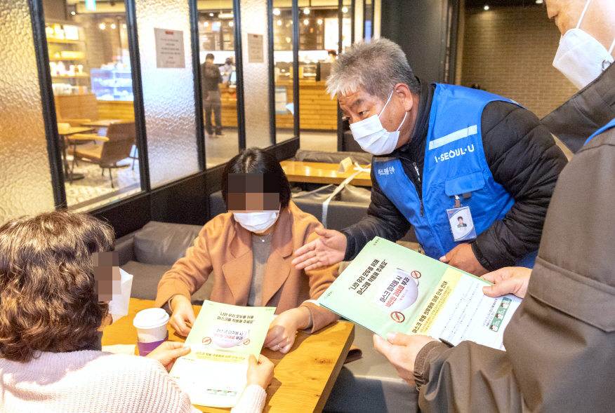 An official from Yancheon-gu, western Seoul, briefs on the face mask mandate to visitors at a cafe in the district on Friday. (Yangcheon-gu)