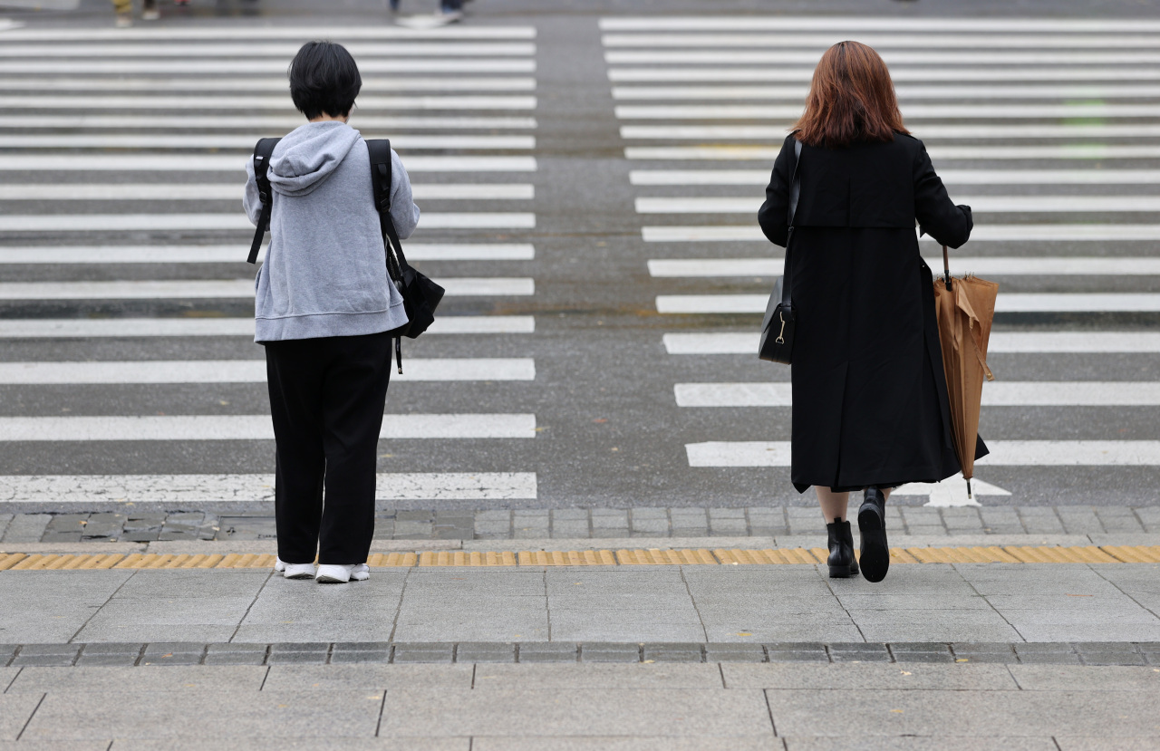 Passersby stand in distance as they wait to cross a road at Gwanghwamun in Seoul. (Yonhap)