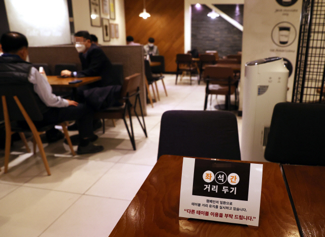 A sign on a table asks customers to use a different table to ensure social distancing at a cafe in Seoul on Wednesday. (Yonhap)