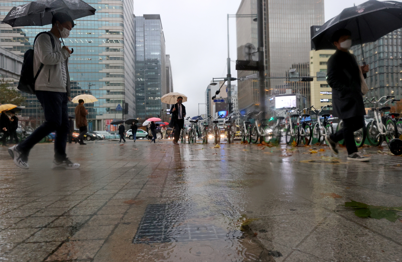 Roads near the Gwanghwamun Square in central Seoul are being flooded Thursday as the capital receives record-level rainfall in the morning. (Yonhap)
