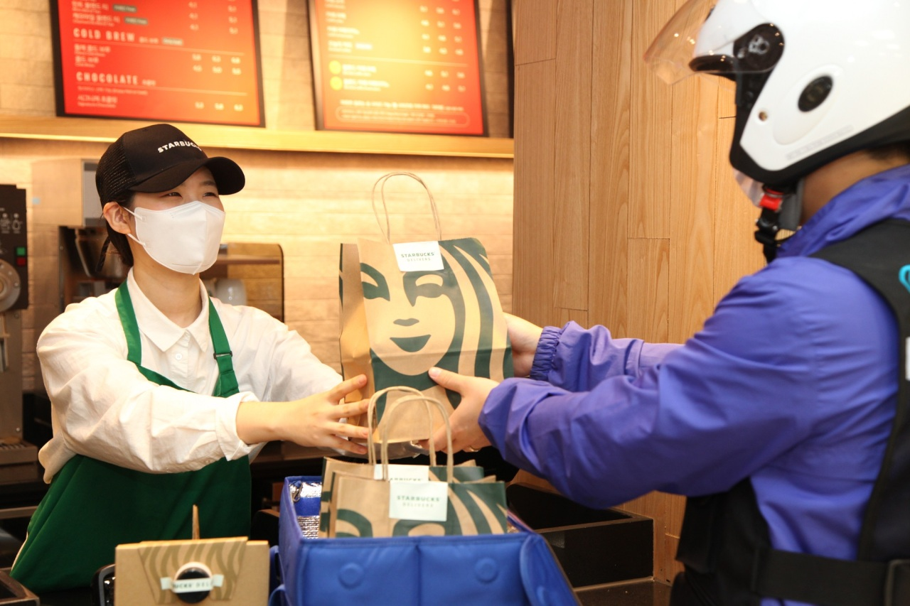 Starbucks Coffee Korea employee hands over the delivery order to a delivery worker. (Starbucks Coffee Korea)