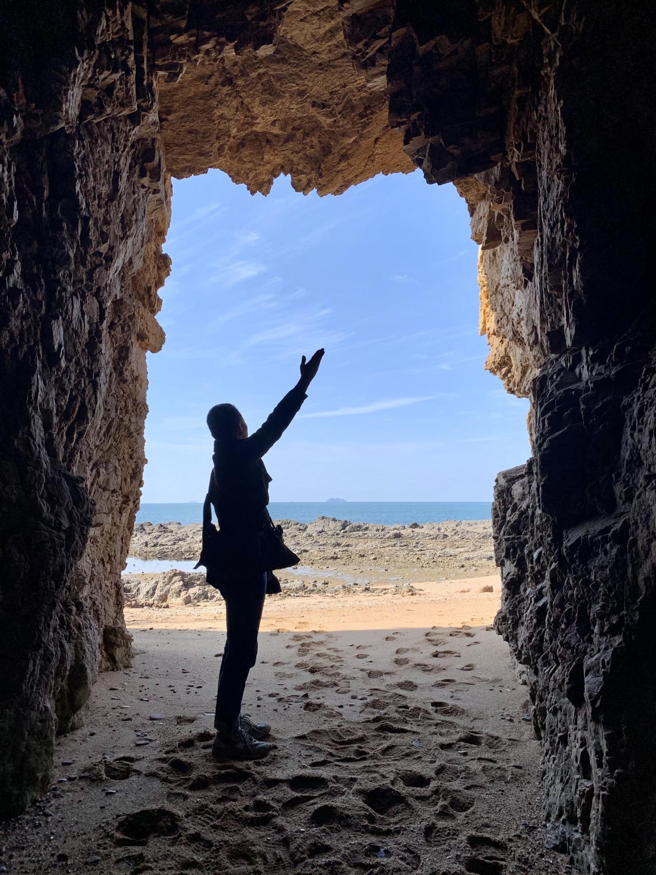 A tourist poses for photos at a cave on Padori Beach. (Im Eun-byel / The Korea Herald)